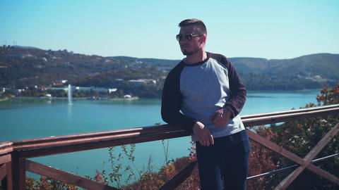 Young sexy man in glasses on a viewing platform overlooking the lake. A man Live Action