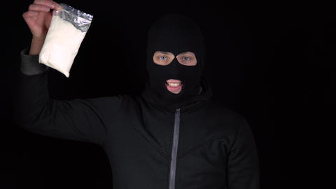 A man in a balaclava mask stands with a pack of heroin. The bandit holds a drug Live Action