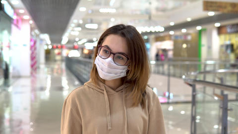 A young woman in a medical mask walks in a shopping center. The masked woman Live Action