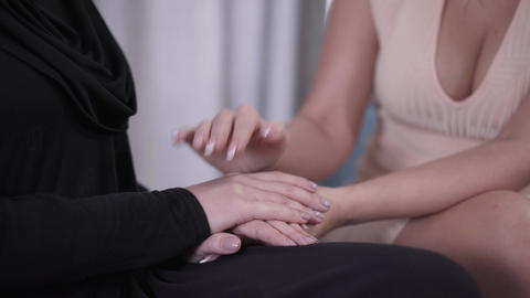 Close-up female hands holding each other. Modern Caucasian woman in candid dress Live Action