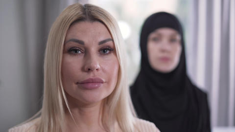 Focus changes from face of modern Caucasian blond woman to young Muslim woman Live Action