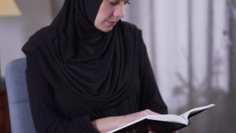 Camera moving up from book to focused Muslim woman reading. Smart modern woman Live Action