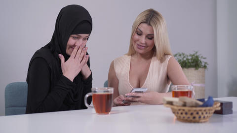 Shy Muslim woman and confident Caucasian lady looking at smartphone screen and Live Action