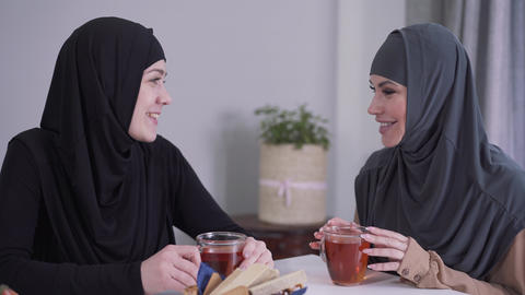 Close-up of two happy Muslim women talking and laughing indoors. Female friends Live Action
