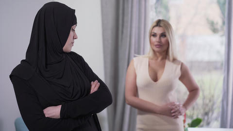 Conservative Muslim woman looking back at modern Caucasian girl in candid dress Live Action