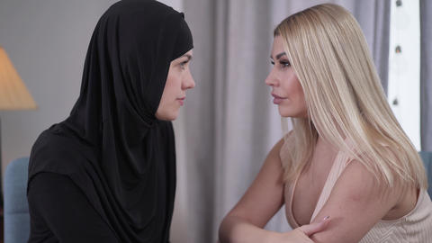 Side view of two women from diverse cultures looking at each other. Muslim Live Action