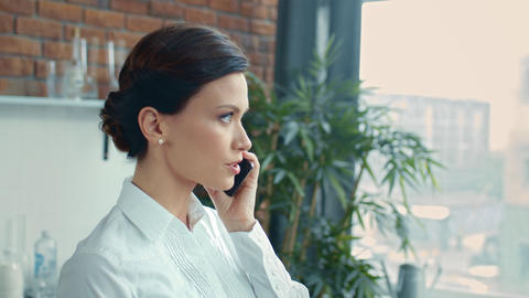 Businesswoman speaking cell phone. Woman looking on daily planner in kitchen Live Action
