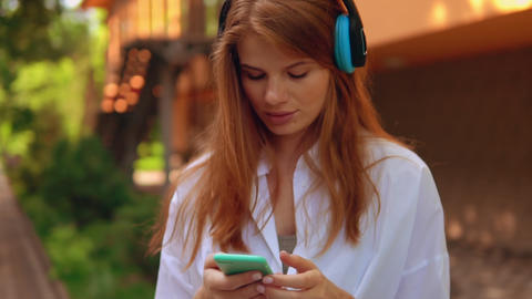 portrait young woman listening music outdoors Live Action