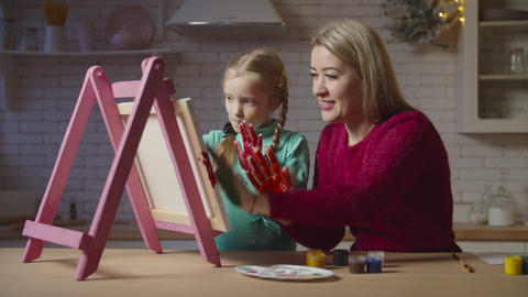 Carefree mother and child painting with hands Live Action