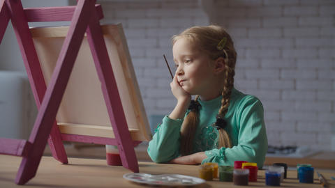Dreamy little girl pondering over future painting Live Action