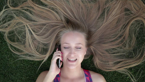Girl with beautiful blonde hair lying on grass Footage