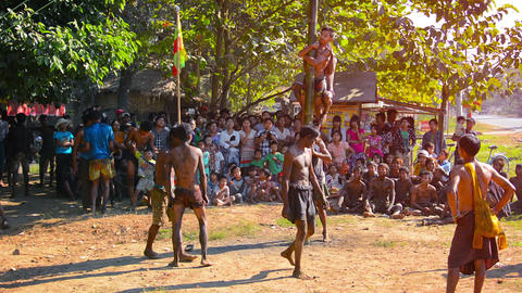 Traditional burmese entertainment competition. Men reach prize on top of pole Footage