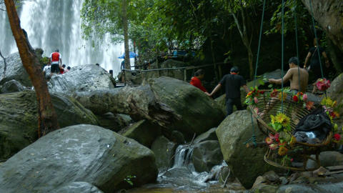 Tourists clamber over the boulders at Phnom Kulen National Park. with sound Live Action