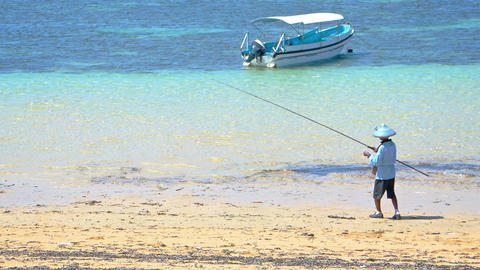 Local Man Carrying a Fishing Rod on a Balinese Tropical Beach. Video FullHD Live Action