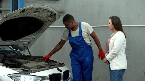 Mechanic shows the motor of car to woman Live Action