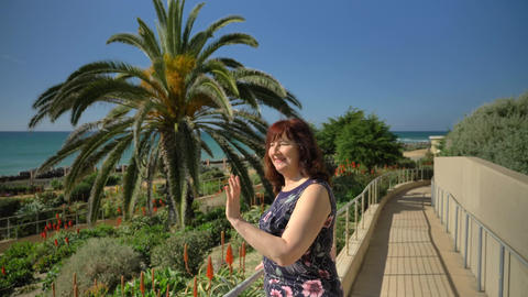 Happy woman waving to friends in Linda Lane Park in San Clemente California Live Action