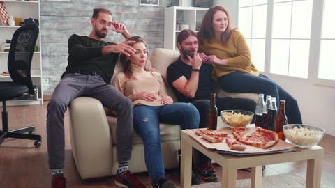 Group of caucasian friends relaxing watching tv sitting on couch Live Action
