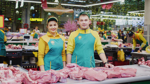 friendly sellers near counter with pork meat at market Live Action
