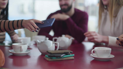Close-up of group of unrecognizable people putting smartphones on the table in Live Action