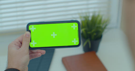 Close up of a man hand holding a mobile telephone with a vertical green screen Live Action