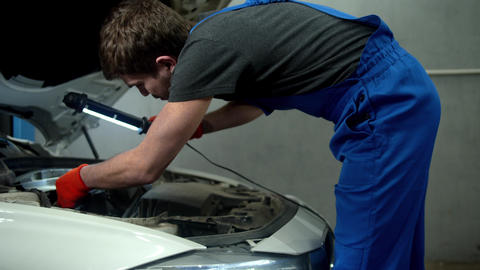 Mechanic with flashlight examines the motor of car Live Action