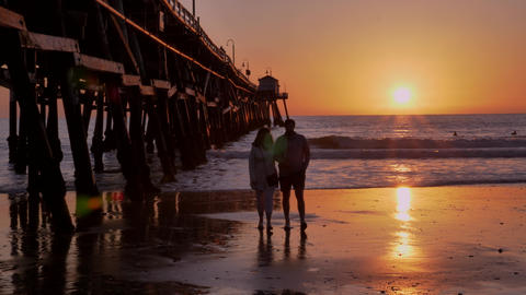 Couple walking at Scenic orange pink Sunset with epic rays of light and sun Live Action