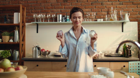 Woman preparing healthy breakfast. Girl putting two yogurt cups on wooden table Live Action