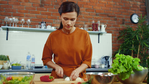 Woman tasting cutted onion bulb. Smiling housewife cooking vegetables Live Action