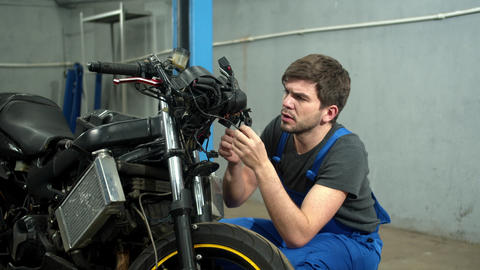 Mechanic tries to repair a motorcycle in auto repair shop Live Action