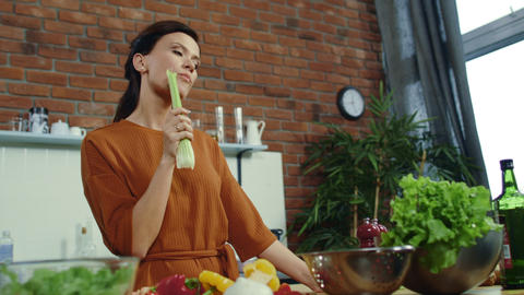 Girl eating fresh celery at home. Young woman getting idea during cooking Live Action