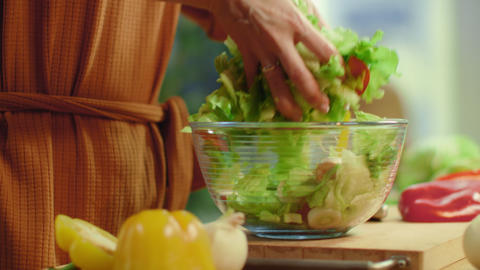 Woman hands tossing vegetable salad. Female cooking fresh healthy meal Live Action