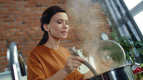 Woman smelling hot soup in kitchen. Housewife cooking meal at home kitchen Live Action