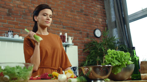 Woman tasting fresh celery in kitchen. Joyful brunette cooking healthy food Live Action