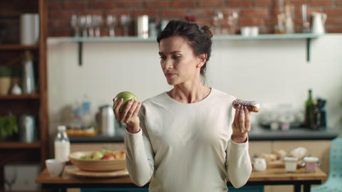 Woman looking between apple and eclair. Brunette girl eating tasty cake at home Live Action