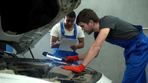 Mechanic examines the motor of car and his collegue takes notes Live Action