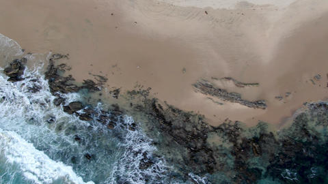 Aerial top view of the ocean waves washing on the coast of the Pacific ocean Live Action