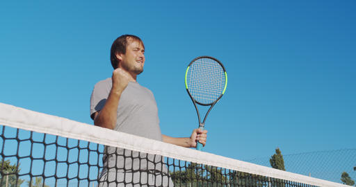 Male athlete playing tennis on outdoors hard court. Happy man in celebration of Live Action