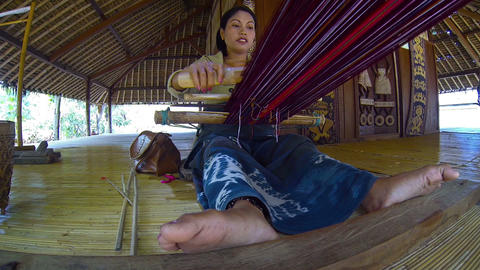 Local woman weaving on a handmade loom in Bali. Indonesia Footage