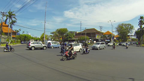 Motorcycle ignores traffic lights to cross busy stream of traffic in Bali Live Action
