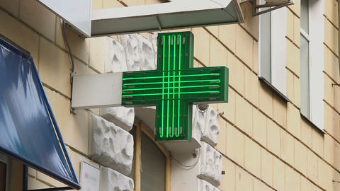 Pharmacy, drug store green neon cross lighted at daytime, city Live Action