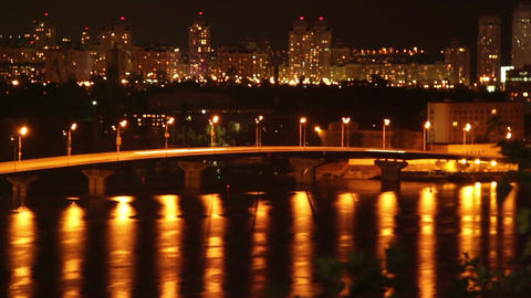 Night sleeping city cars drive on bridge yellow light reflection Footage