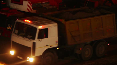 Construction yard trucks drive, working machines, night site Footage
