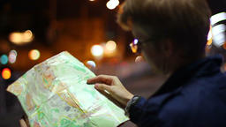 Male looking for route in tourist map foreign city night Footage