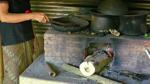 Balinese woman roasting coffee beans in a cast iron pan. over a wood fire stove Archivo