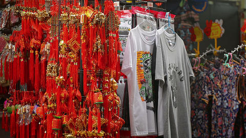 Clothes. souvenir t-shirts and. chinese good luck charms at street stall Live Action