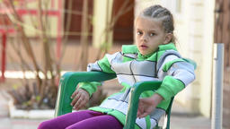 Seven-year girl thoughtfully sitting on a chair and smiling happily seeing somet Footage