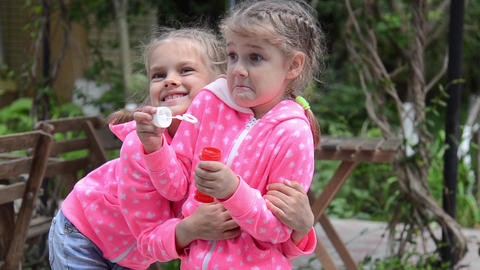 Girl blowing bubbles, suddenly her arms around the other girl, and together they Footage