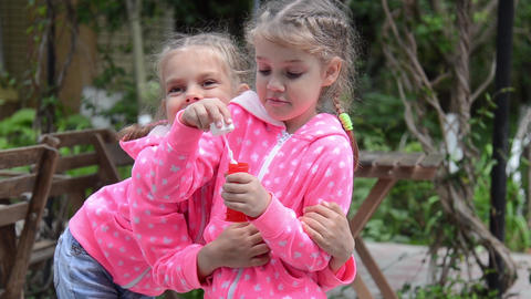 Girl blowing bubbles, suddenly her arms around the other… Stock Video Footage