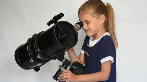 Seven-year girl looks in a reflector telescope Footage