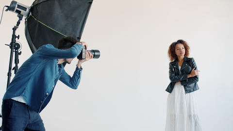 Mixed race model posing for camera in studio and photographer taking photos with Live Action